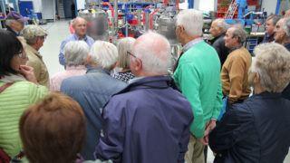 Georg Senftl (Geschäftsführer bei ViscoTec) mit einem Teil der Besucher in der ViscoTec Montagehalle.
