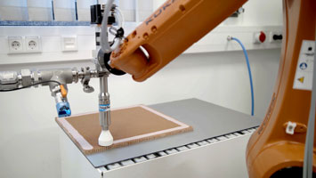 ViscoTec dispenser during the fully automated filling of a honeycomb structure, which is installed in aircraft cabins, for example.